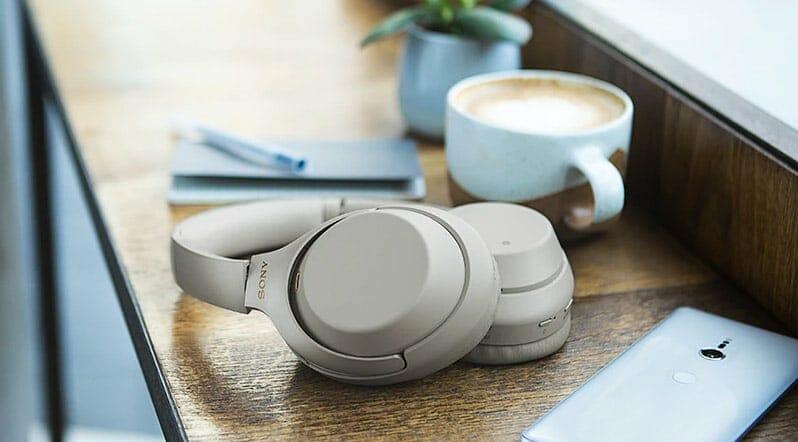 Perfektes Trio: Sony WH-1000XM3, Smartphone und ein Cappucino